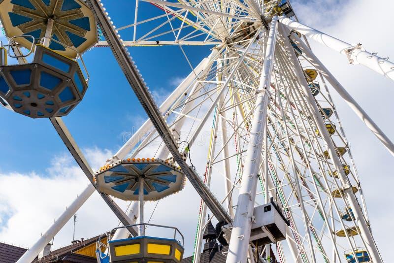 Pariserhjul med färgrika gondoler i en funfair, mot en härlig blå himmel med vita moln arkivbilder