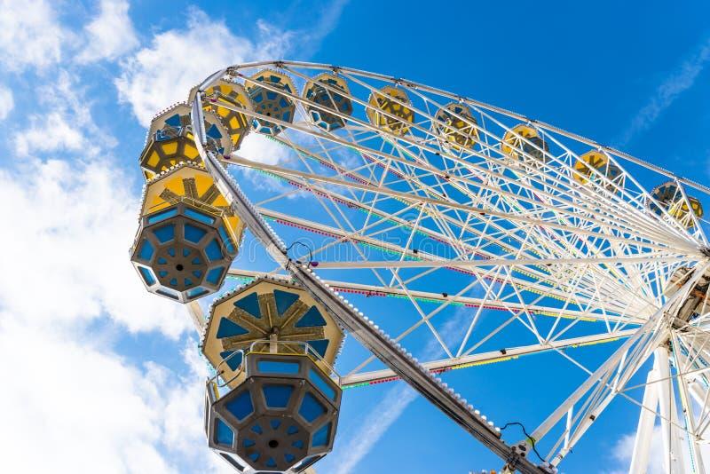 Pariserhjul med färgrika gondoler i en funfair, mot en härlig blå himmel med vita moln arkivbild