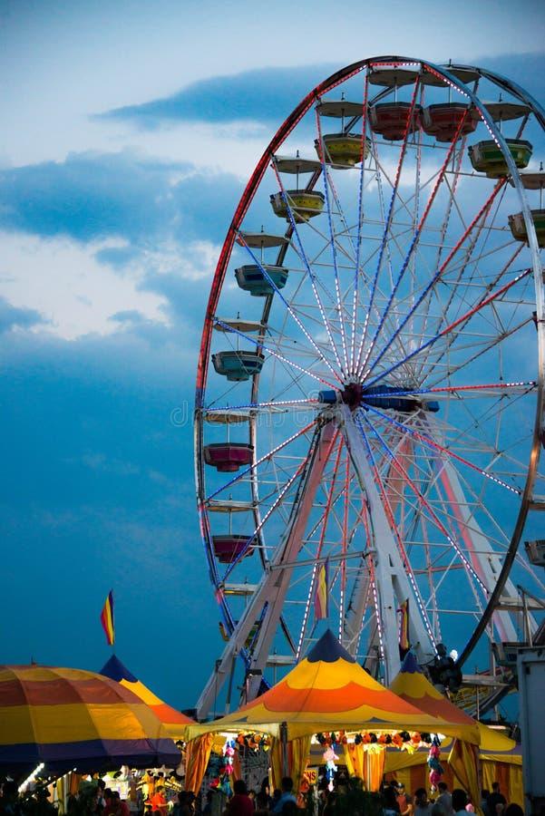 Pariserhjulkarnevalritt och färgrika tält på en mässa arkivfoton