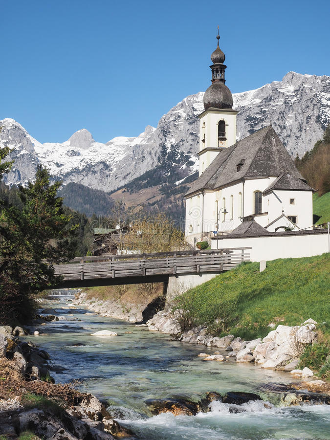 Parish church St. Sebastian in Ramsau, Bavarian Alps, Germany. Church Saint Sebastian with creek in the foreground and Bavarian Alps in the background royalty free stock photos