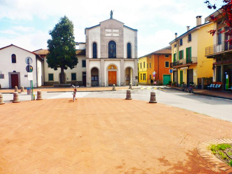 Parish of San Michele, Agliana, Tuscany, Italy. Piazza in front of Parish of San Michele surrounded by colored homes in Agliana, Tuscany, Italy on sunny day stock photo