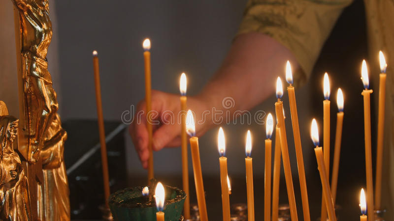 The parishioner put a candle inside an Orthodox church. Close up royalty free stock image