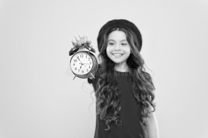 Parisian child on yellow. beauty hairdresser. child with alarm clock. Timeless fashion. happy girl with long curly hair stock images