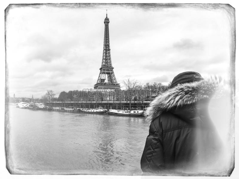 Parisian French man watching the flooding swollen Seine river. Rear view of Unrecognizable Parisian senior man watch swollen river Seine near Eiffel Tower as royalty free stock photography