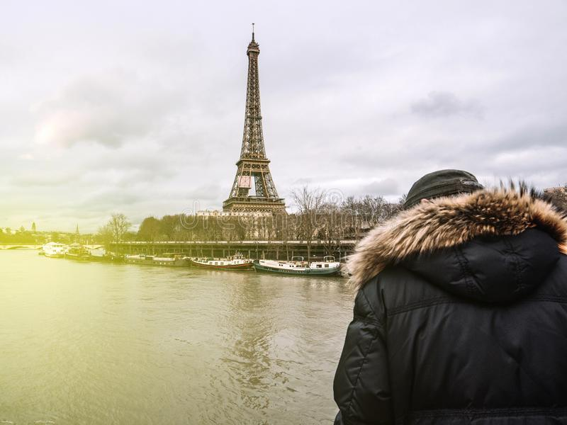 Parisian French man watching the flooding swollen Seine river. Rear view of Unrecognizable Parisian senior man watch swollen river Seine near Eiffel Tower as stock photography