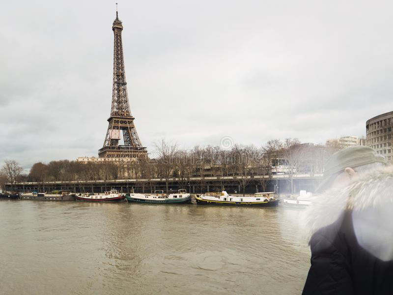 Parisian French man watching the flooding swollen Seine river. Unrecognizable Parisian senior man watch the swollen river Seine near the Eiffel Tower as the stock image