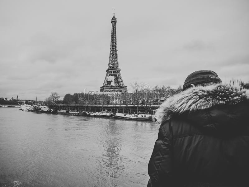 Parisian French man watching the flooding swollen Seine river. Unrecognizable Parisian senior man watch the swollen river Seine near the Eiffel Tower as the royalty free stock photo