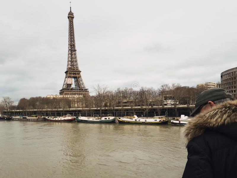 Parisian French man watching the flooding swollen Seine river. Unrecognizable Parisian senior man watch the swollen river Seine near the Eiffel Tower as the royalty free stock images