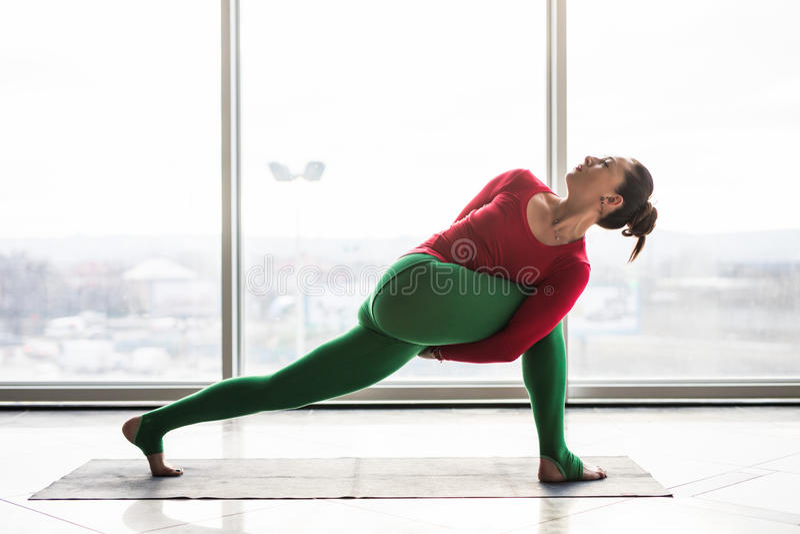 Parivritta parsvakonasana. Beautiful yoga woman practice in a big window. Hall background. Yoga concept stock photography