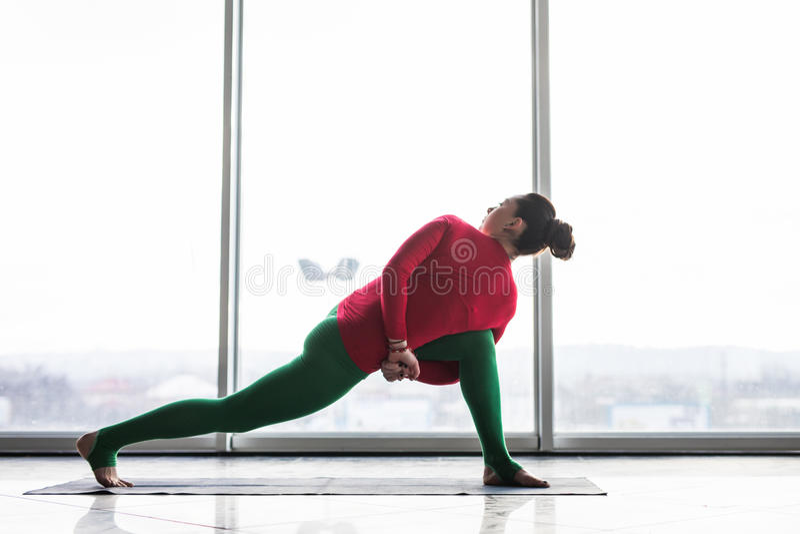 Parivritta parsvakonasana. Beautiful yoga woman practice twist poses in a big window hall. Background. Yoga concept stock photos