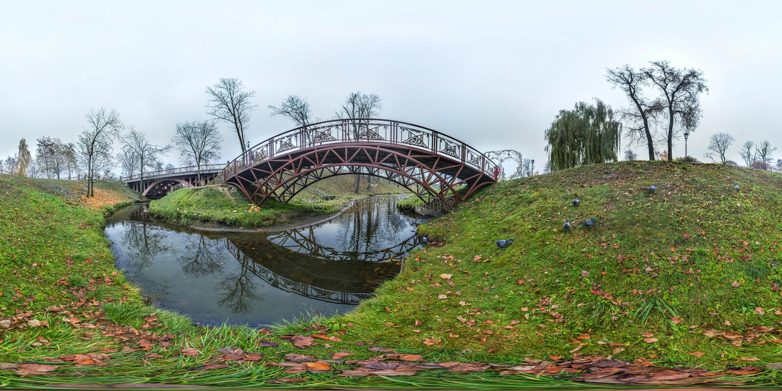 Park at autumn with dark sky, river and bridge Ugly landscape. 3D spherical panorama with 360 degree viewing angle Ready for virtu. Park at autumn with dark sky stock images