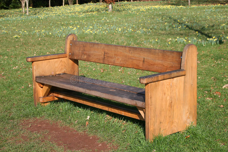 Park bench. Wooden park bench on grass royalty free stock photos