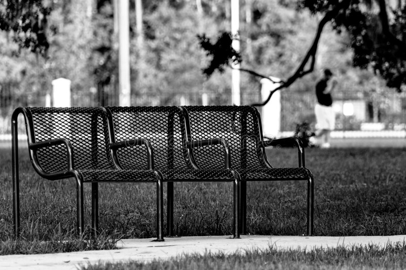 Park bench. A bench in Losco Park with man in background in black and white stock image