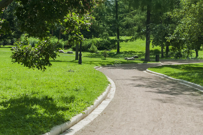 Park Bench and Alley in park outdoors. Public Park , Bench and Alley in park outdoors in sunny summer day stock photo