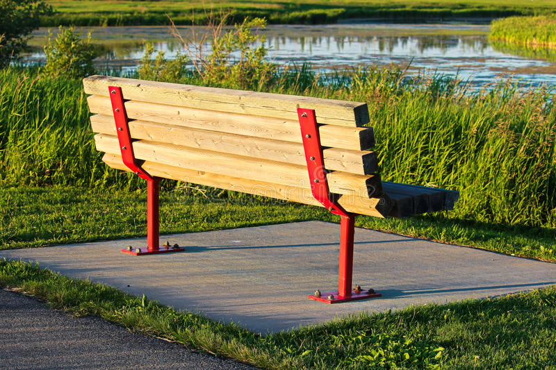 A park bench on a concrete base overlooking a scenic marsh stock photography