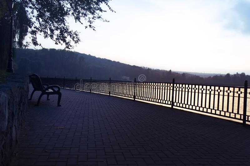 Park bench by the lake at sunset day stock photo