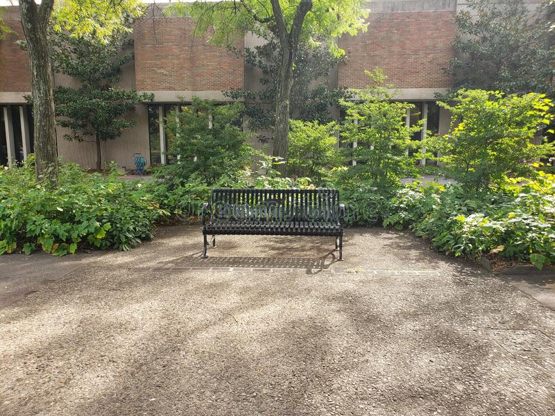 A park bench in the middle of Campus for people to sit and take a break out in the middle of class stock image