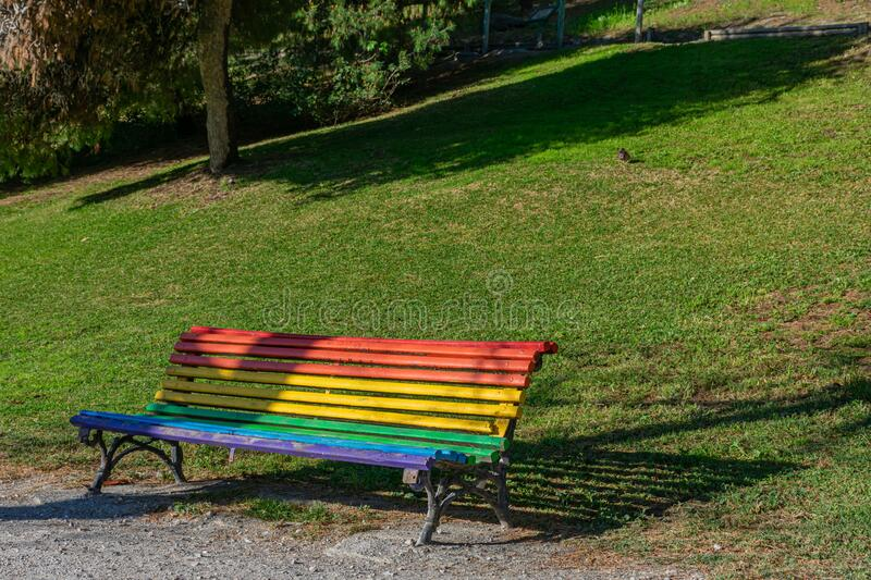 Park bench with rainbow colors. In reference to the homosexual world stock images