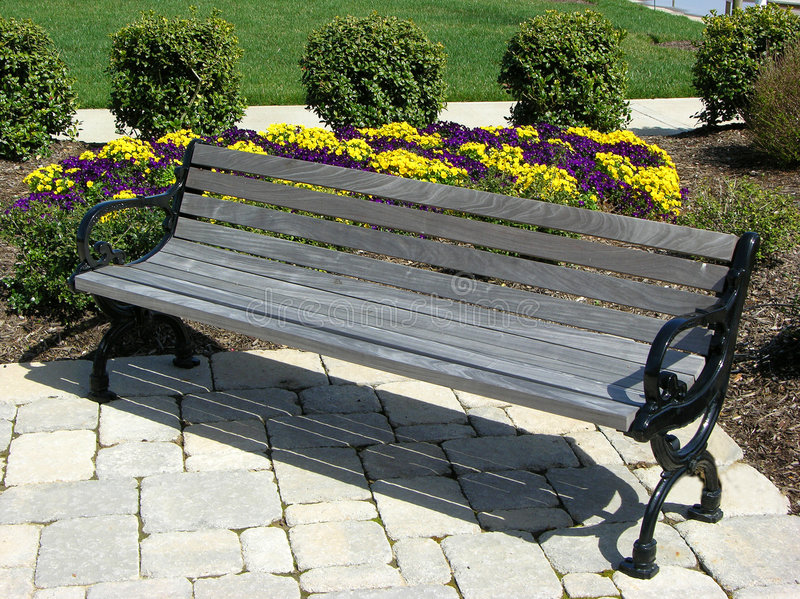 Park Bench On Stone Patio. With yell and purple flowers royalty free stock images