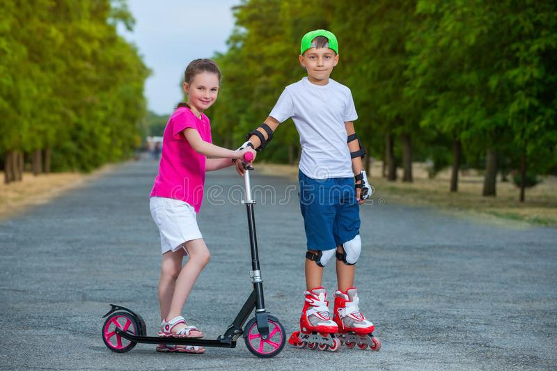 In the park the boy rolls on rollers and the girl rolls on a scooter royalty free stock photo