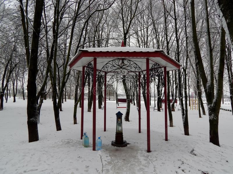 In the park built a pump room and a gazebo above it. The snow that fell out covered the ground with white carpet, the trees, the beretka. People come to the royalty free stock images