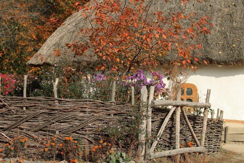 Park in de Oekraïne beeld van een oud huis met een stro op het dak Rond het huis is een rieten omheining Bloeit overal waar en bo royalty-vrije stock fotografie