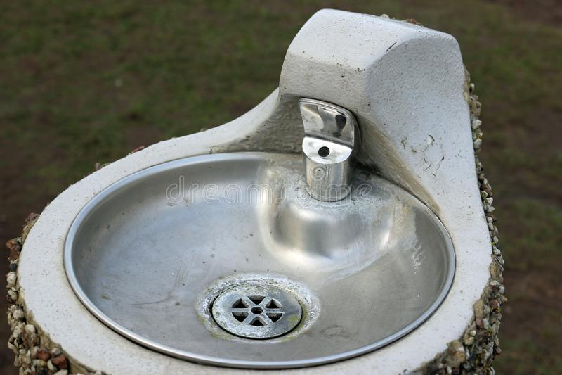 Park drinking fountain. Metal park drinking fountain with bowl on a concrete plinth with a pebble dashed exterior stock photo