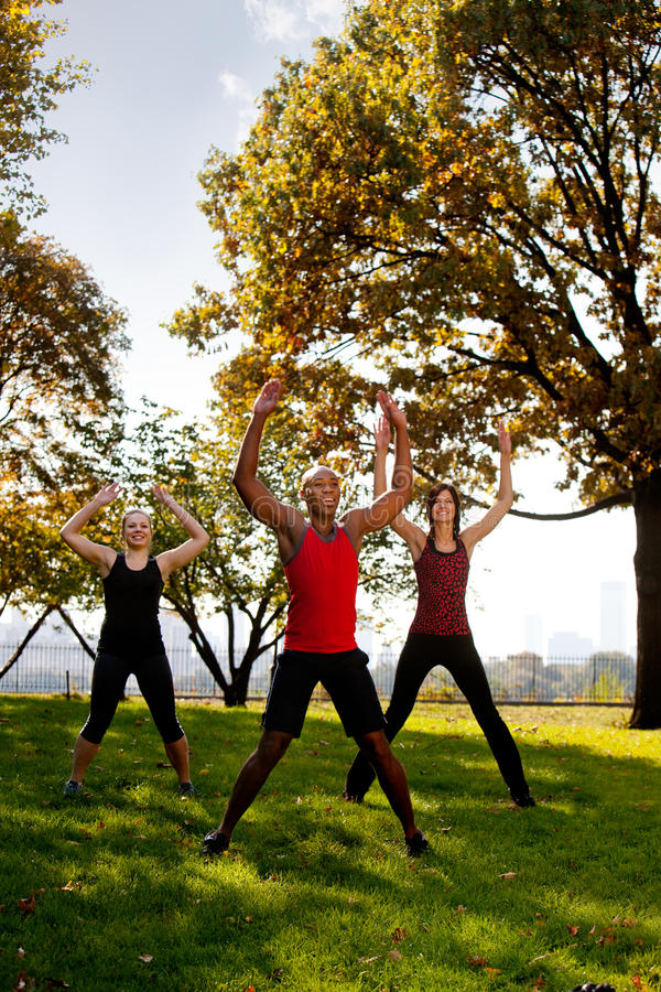 Park Exercise. A group of people doing jumping jacks in the park stock photo