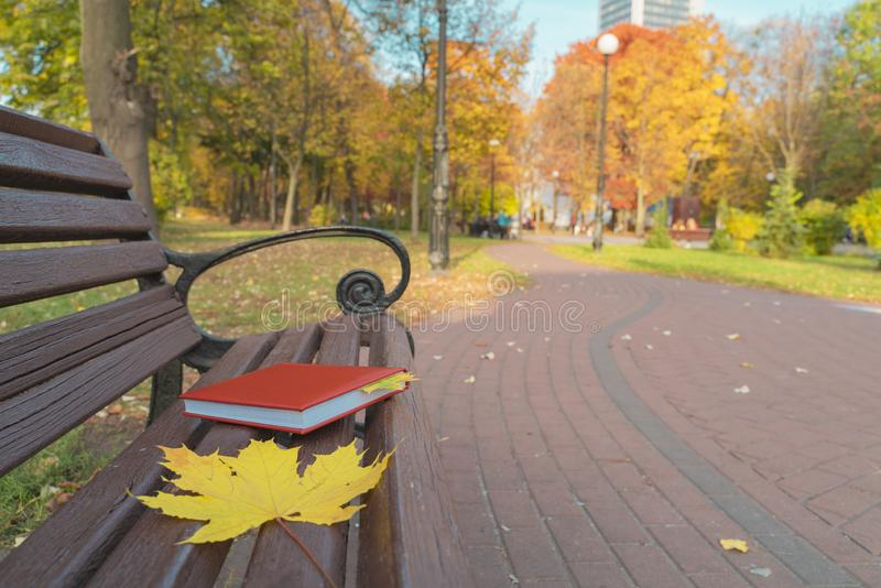 In the park, fallen leaves lie on a wooden bench along with red notebook. Notebook bookmark is autumn leaves. In the background royalty free stock photos