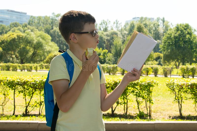 In the park, in the fresh air, the boy in glasses and with a backpack, enthusiastically reading a book and eating an apple stock image