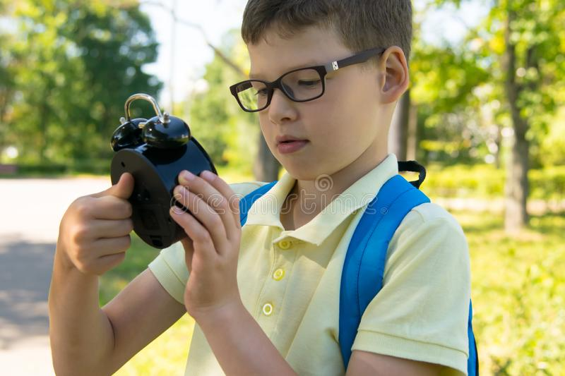 In the park, in the fresh air, close-up, schoolboy starts an alarm clock to catch the lesson royalty free stock image