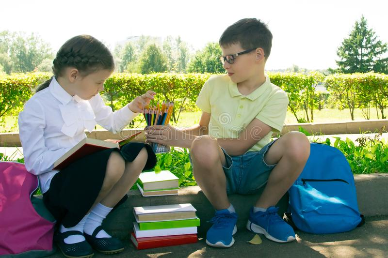 In the park, in the fresh air, schoolchildren do their homework, the boy gives the girl a glass with pencils stock photo