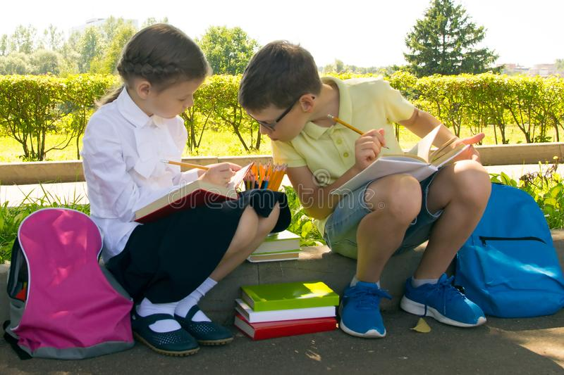In the park, in the fresh air, schoolchildren are doing their homework, the boy is peeping at the girl's decision stock photo
