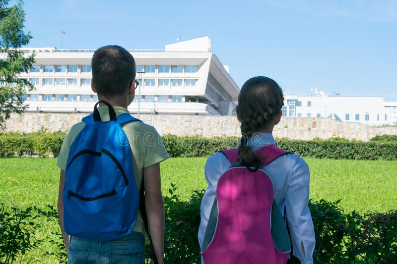 In the park, in the fresh air, schoolchildren look at the educational institution, rear view royalty free stock photo