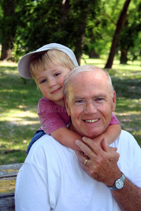At the Park with Grandpa. Young boy hugs his grandfather on summer outing in the park