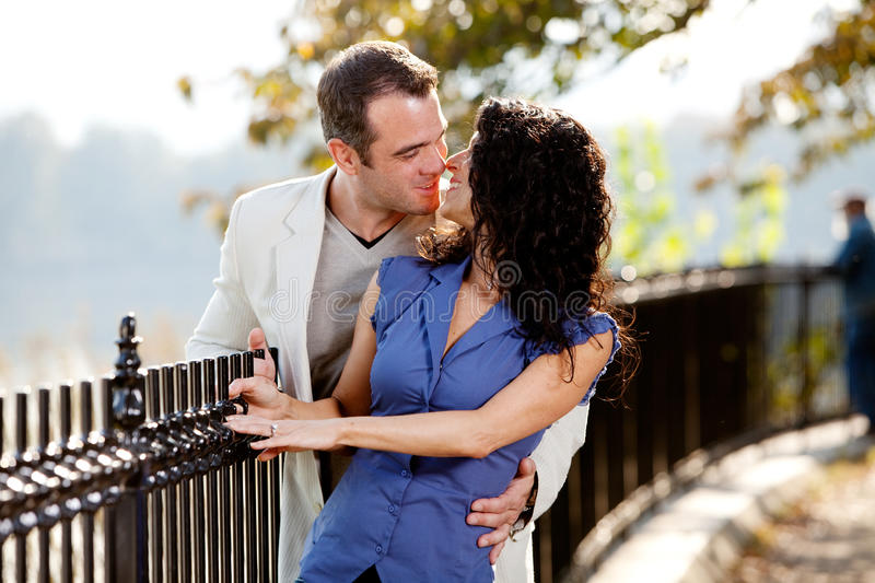 Park Kiss. A happy couple kissing in the park on a beautiful day royalty free stock photos
