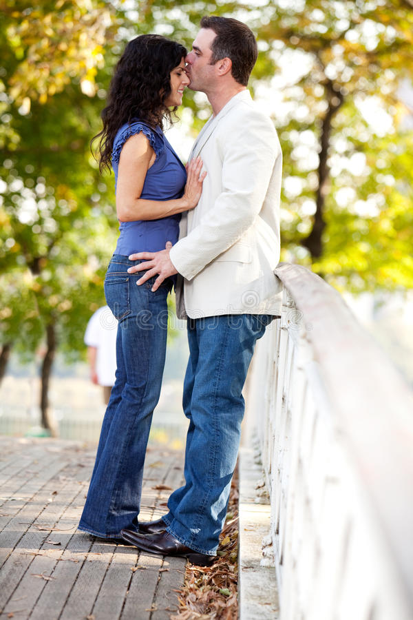 Park Kiss. A man kissing a woman on the forehead stock image