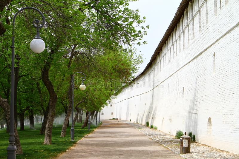 Park lane at the old white brick fortress or castle wall. Park lane at the old white fortress or castle wall stock photo