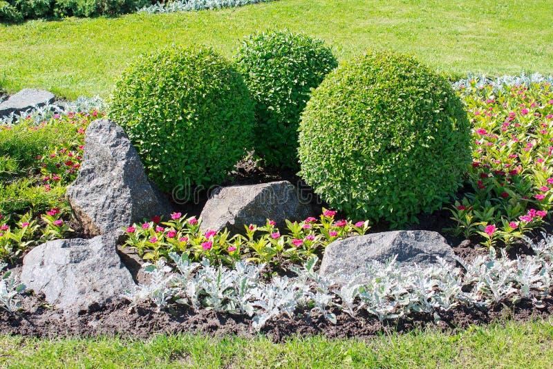 Park met struiken en stenen stock afbeelding