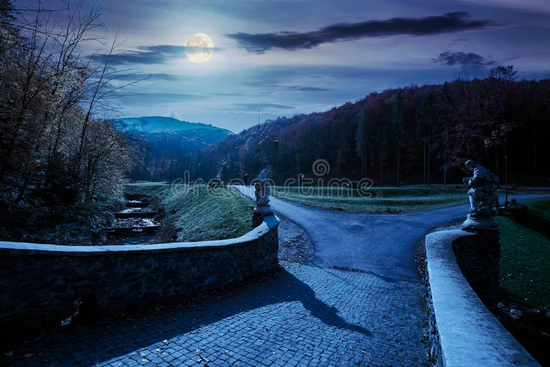 Park among mountain in autumn at night. In full moon light. trees in colorful foliage, vivid grassy green lawns. walking path to the bridge through creek royalty free stock images