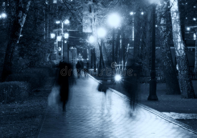 Park night alley silhouettes. Park night silhouettes: a view of a alley / walkway / pathway in a park alight by lanterns / lamps / streetlight with trees, people stock images
