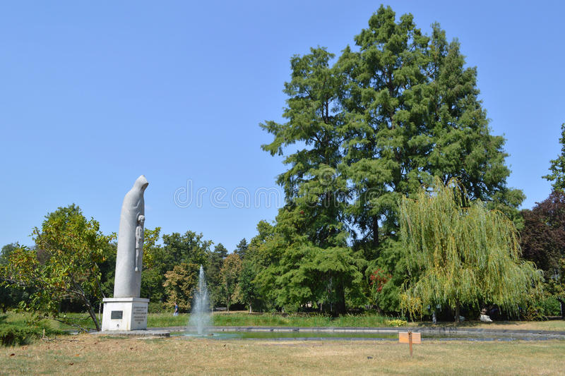 Park - Novi Sad. Park in Novi Sad with lush vegetation, a small artificial lake and a fountain in it, a beautiful monument made of white stone of the sunlit the royalty free stock images