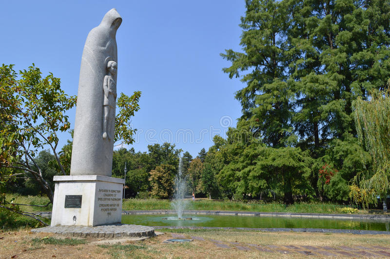 Park - Novi Sad. Park in Novi Sad with lush vegetation, a small artificial lake and a fountain in it, a beautiful monument made of white stone of the sunlit the stock photos