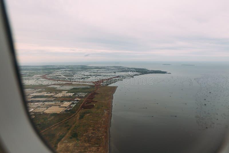 Park przemysłowy w poza śródmieściem pobliskim brzeg Dżakarta, Indonezja Widok z lotu ptaka fabryki, domy i morze od samolotu, fotografia stock