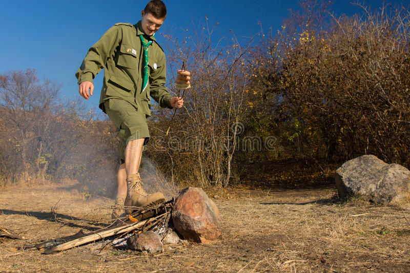 Park ranger stamping out a cooking fire. Park ranger or scout stamping out a cooking fire with his booted foot after cooking sausages for his lunch, with royalty free stock image