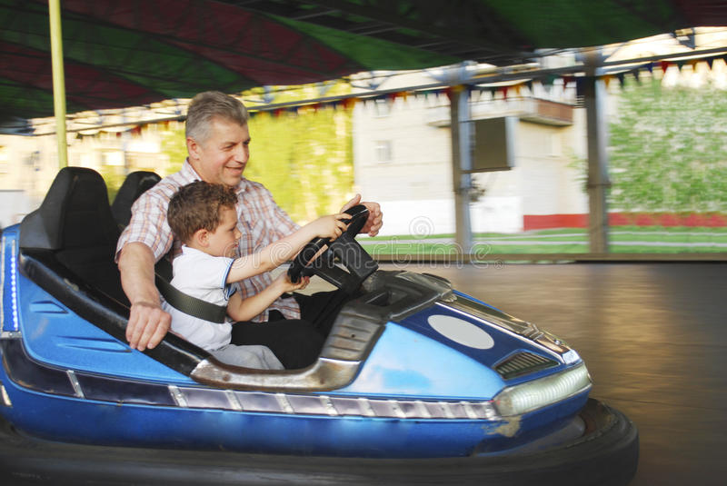 In the park on the rides grandfather with his grandson go by car royalty free stock photos