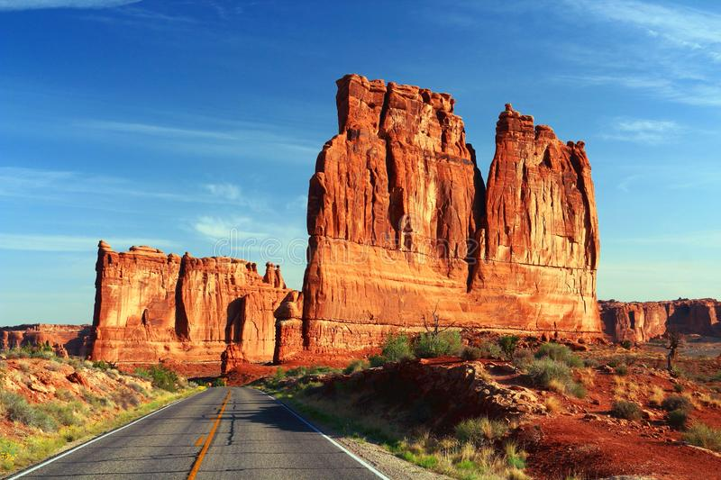 Morning Sun on the Towers of Babel, Arches National Park, Utah, Southwest, USA. The park road through the Southwest desert landscape is dwarfed by the imposing stock image