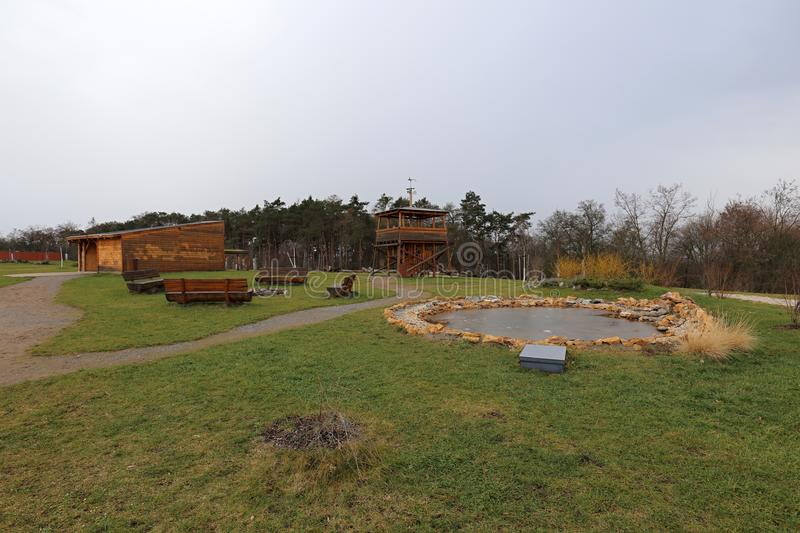 Park with small pond, outlook tower and wooden shed. In autumn stock photography