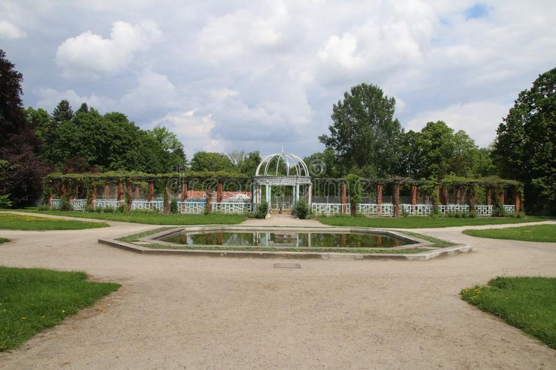 Paths and fountain in a park with symmetrical architecture on a cloudy warm day. Park and symmetrical composition of paths with fountain in the centre and stock photos
