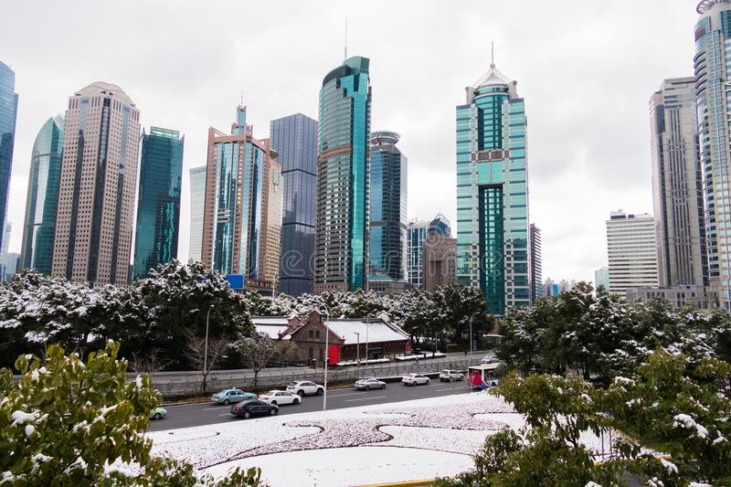 Park with trees and road covered with snow surrounded by skyscrapers in the Pudong area. Shanghai, China stock image